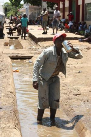 A resident of flood-hit Chokwe, in southern Mozambique, takes a drink of drain water, on January 27, 2013