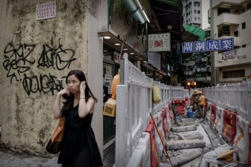 A woman blocks her ears as she walks past roadworks in Hong Kong on July 9, 2013