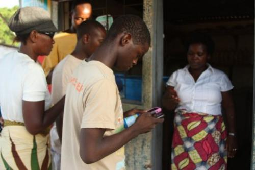 People pick up bottles of chlorine after receiving on their mobile phones a code, on February 12, 2013, in Mozambique