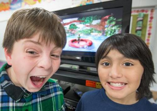 Sawyer Whitely (L), 10, and Michael Mendoza, (also 10), who are autistic, pose for a photo while playing selected games on a Mic