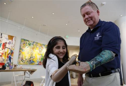 Afghan girl who lost arm paints with prosthetic