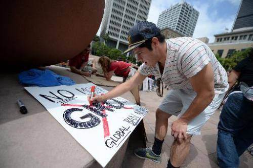 An activist makes a sign before a protest against chemical giant Monsanto, in Los Angeles, California, on May 25, 2013