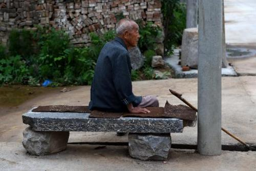 An elderly man rests on a seat in Weijian village, in China's Henan province on July 30, 2014