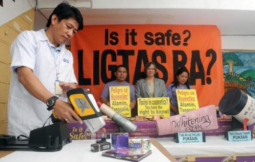 An engineer (L) from the EcoWaste Coalition checks cosmetics products for lead content in Manila on March 14, 2012