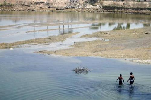 Iraqis wade in the waters of the Euphrates River in Hindiya on May 19, 2009
