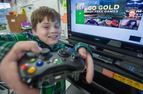 Sawyer Whitely, who is autistic, holds the contoller as he plays selected games on a Microsoft X-box Kinect, at Steuart W. Welle